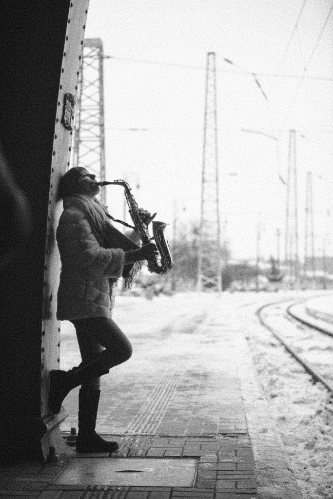 Woman plays the saxophone against the background of an old iron wall at the train station